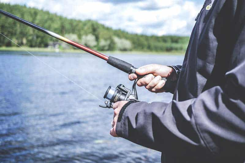 person holding black and red fishing reel