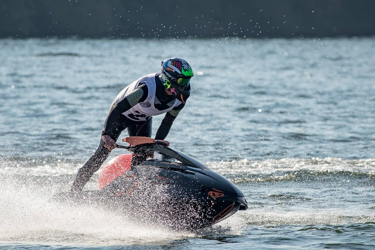 man with helmet standing up while riding jet ski