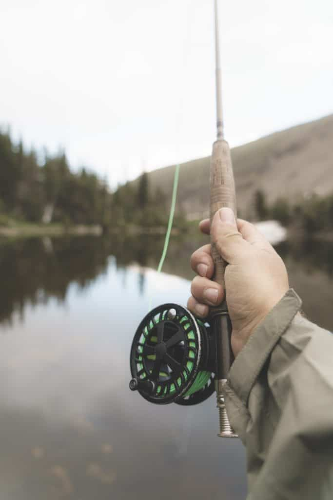 a person showing the handle of a fishing rod